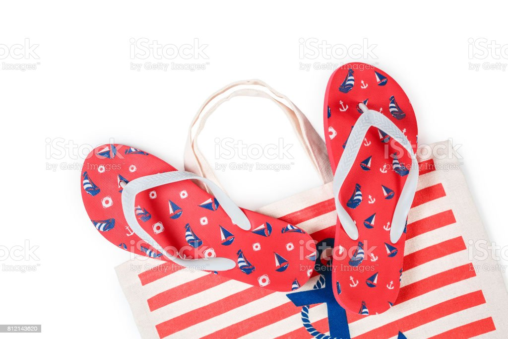 bd99dd9bd Set of Red flip flops and colorful striped print beach bag isolated on  white background. Top view - Stock image .