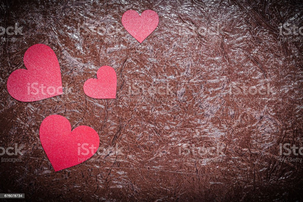 Set of red paper hearts on brown background Valentine card stock photo