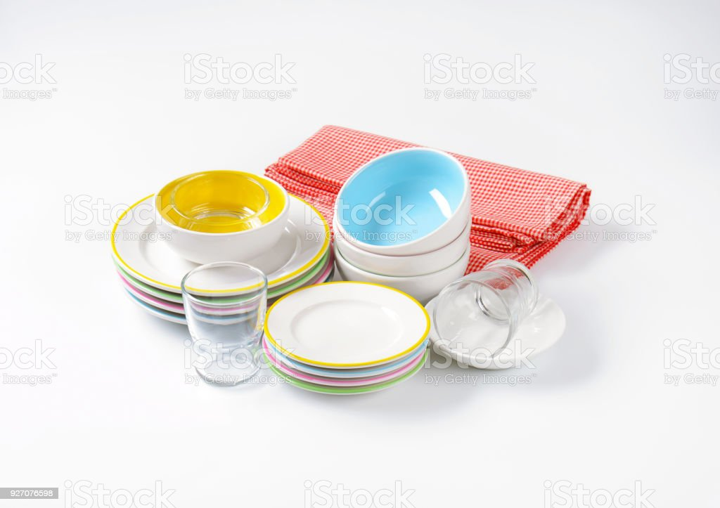 set of rimmed plates, bowls and glasses stock photo