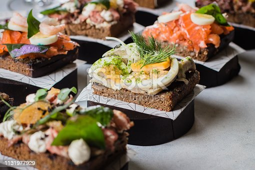 istock Set of scandinavian snack. Smorrebrod. Traditional Danish open sanwiches, dark rye bread with different topping 1131977929
