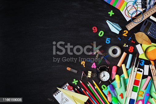 925244914 istock photo Set of school stationery, alarm clock and supplies on blackboard background. Back to school concept. Top view. 1166159005