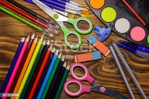Set of school stationery supplies. Colored pencils, watercolor paints, paintbrushes, pens, scissors, eraser, sharpener on wooden desk. Back to school concept