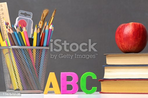 istock A set of school supplies. A stack of textbooks, an apple, letters of the alphabet A, B, C, pencils, brushes, paints against a black chalkboard. The concept of education. Copy space. 1147570135