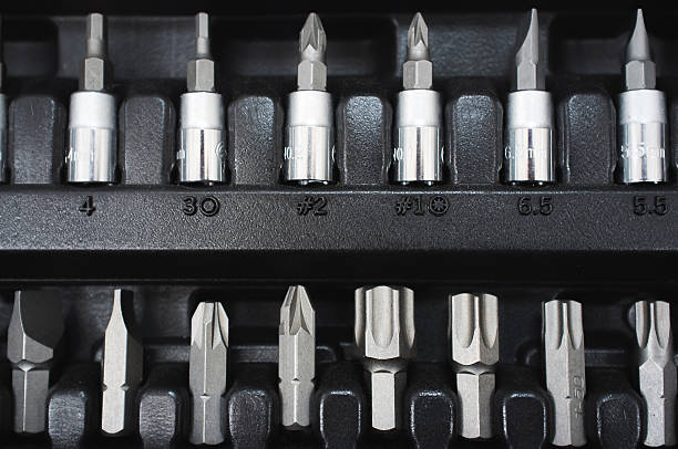 Set of screwdriver bits on toolbox Set of screwdriver bits on socket toolbox. Closeup precision small tools on black background drill bit stock pictures, royalty-free photos & images