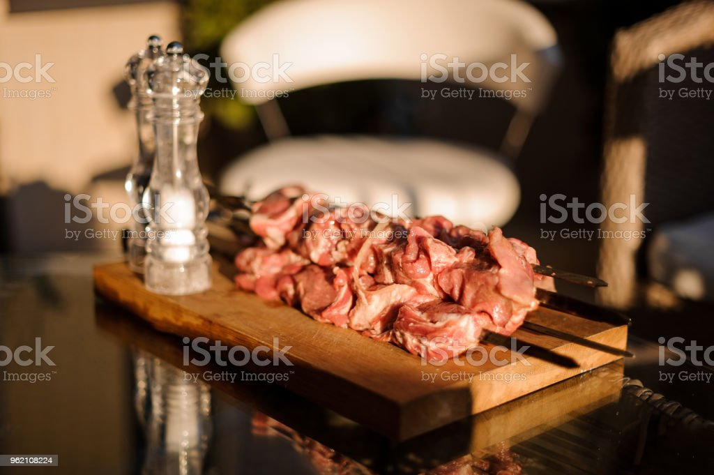 Set of skewers with stringed pieces of fresh meat and salt shaker arranged on the fooden desk stock photo