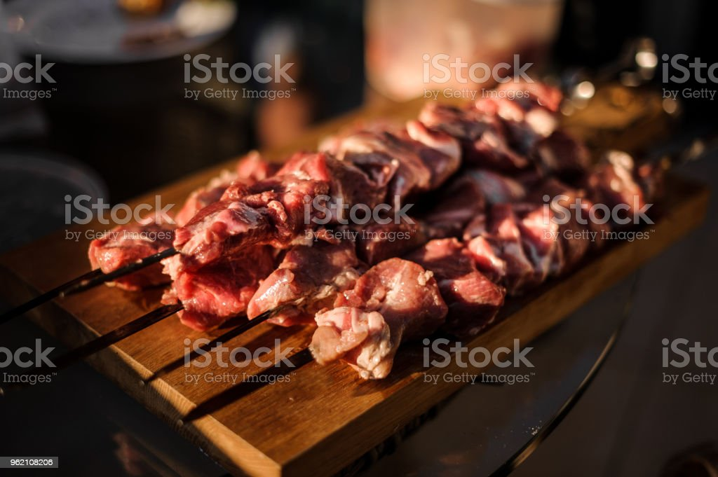 Set of skewers with stringed pieces of fresh meat arranged on the fooden desk stock photo