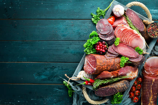 Jogo da carne fumada e secada presunto, carne jerky, salgada do biltong, especiarias e ervas. Vista superior. Espaço livre para o seu texto. - foto de acervo