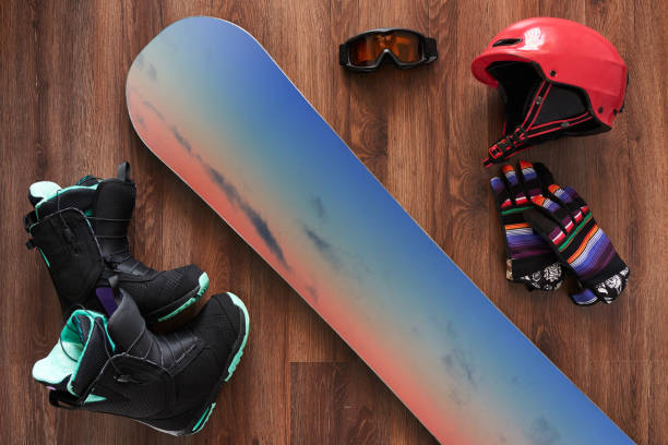 set of snowboard boots, helmet, gloves and mask on wooden stock photo