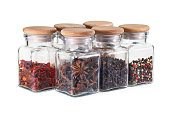 Set of spice jars with spices: peppers mix, cloves, anise star, paprika. White background. Isolated, close-up.