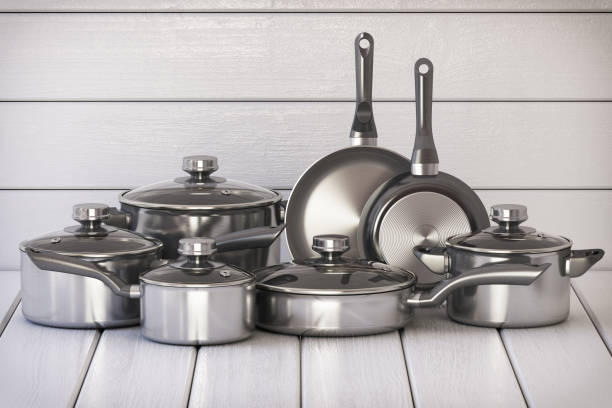 Set of stainless pots and pan with glass lids on the white wooden background stock photo