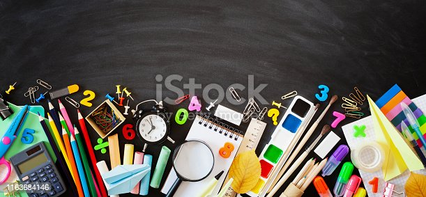 istock Set of stationery, alarm clock and supplies on blackboard background. Back to school concept. Banner format. Top view. 1163684146