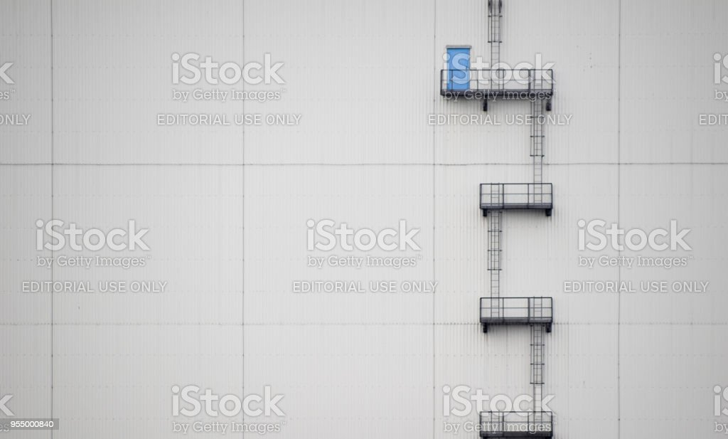A set of steps lead from a blue door in the side of a Warehouse on Zebrugger docks stock photo
