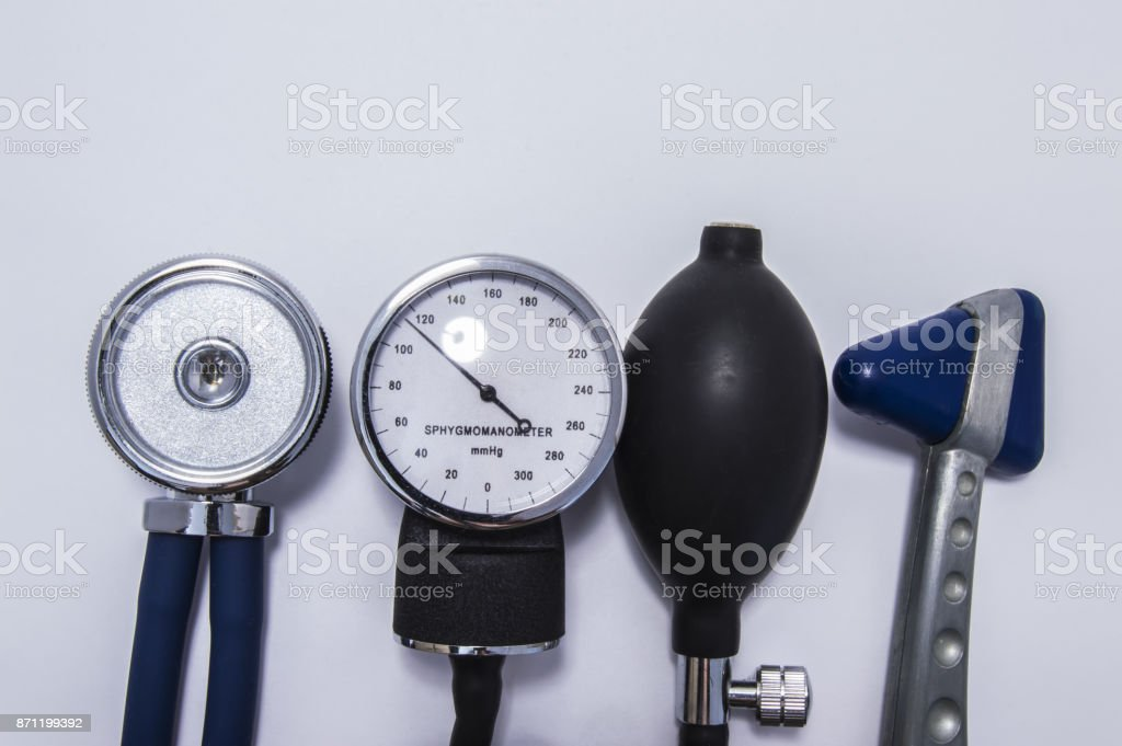 Set of stethoscope with diaphragm upwards, sphygmomanometer, air inflating bulb and neurological reflex hammer on medical table. Kit for doctor for initial diagnosis in internal medicine and neurology stock photo