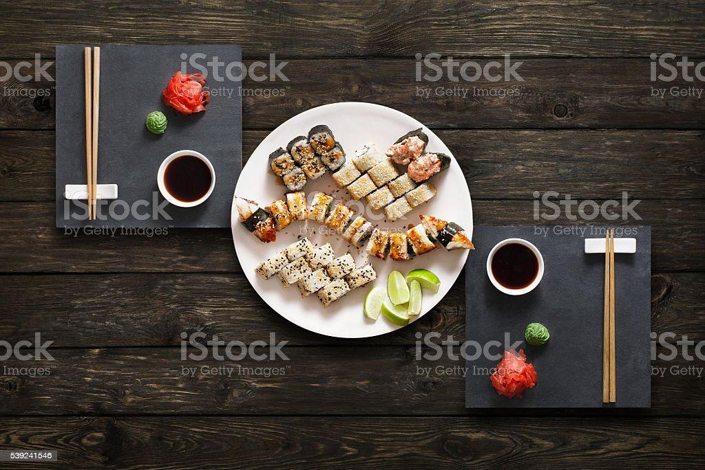 Conjunto de maki sushi y rollos en negro, madera rústica. foto de stock libre de derechos