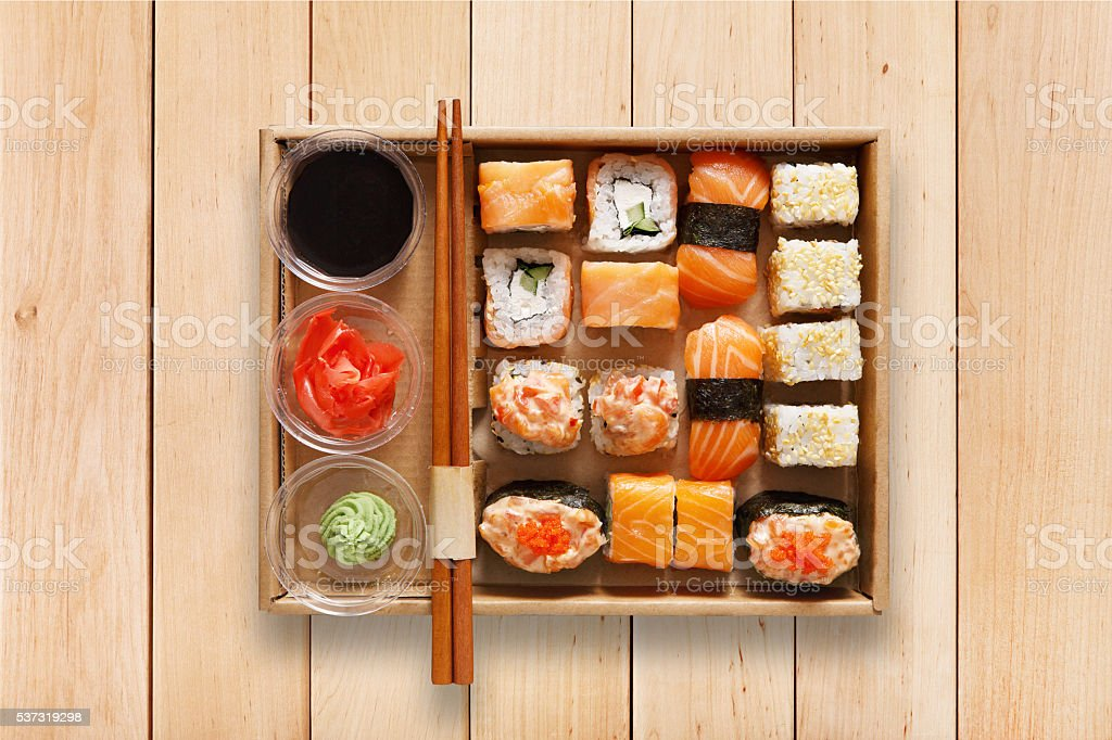 Set of sushi maki and rolls at box on wood. stock photo