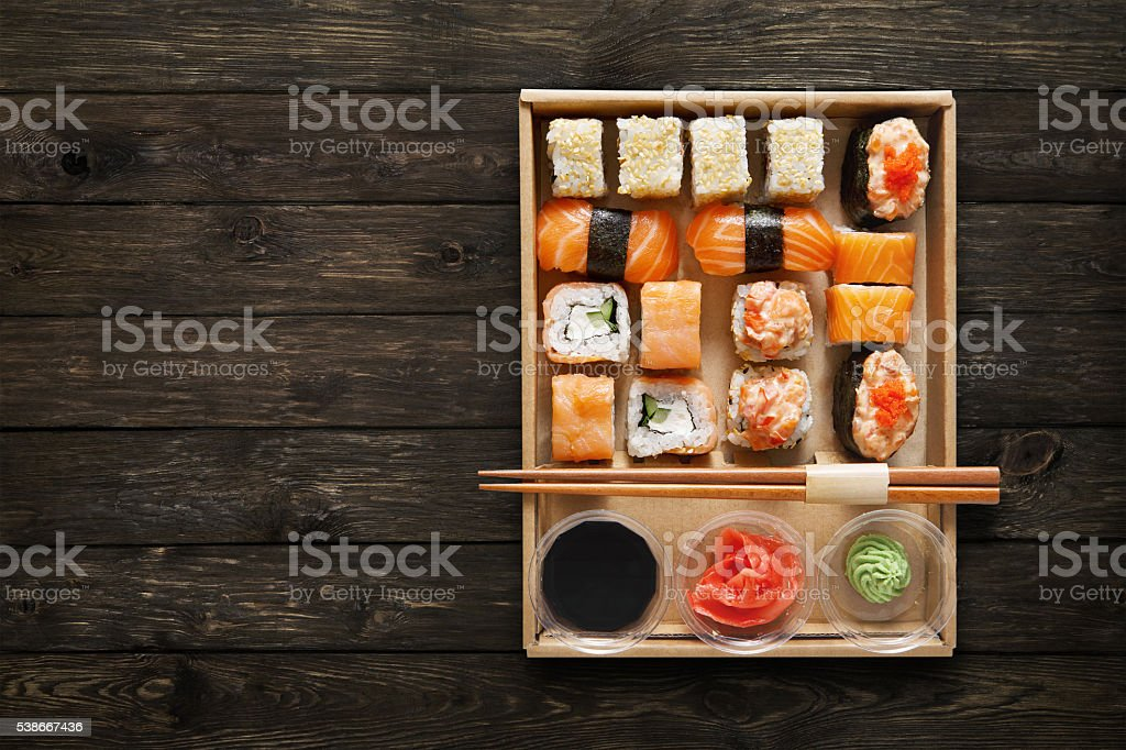 Set of sushi maki and rolls at box on wood. stock photo