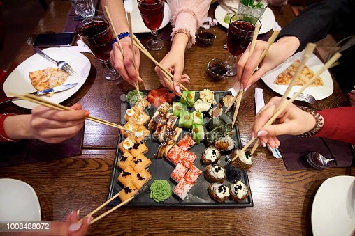 istock A set of sushi rolls on a table in a restaurant. A party of friends eating sushi rolls using bamboo sticks. 1008488072