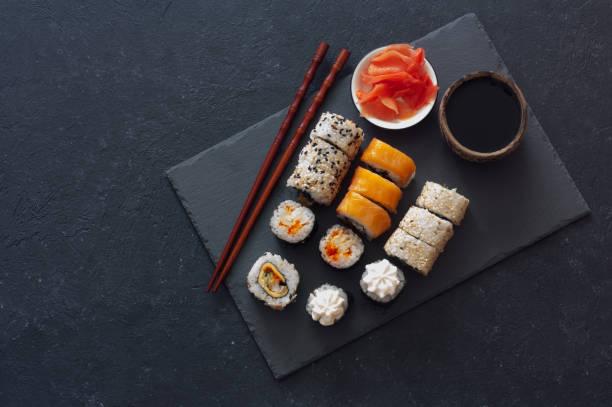 Set of  sushi rolls served on stone slate stock photo