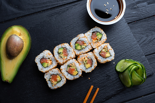 Set of sushi rolls with cream cheese, rice and salmon on a black board decorated with soy sauce and avocado on a dark wooden background. Japanese cuisine. Food photo background