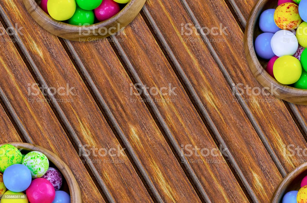 set of sweets round yellow blue pink in bowls a lot bonbon covered with icing on an inclined wooden table stock photo