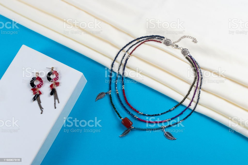 Set Of Tassel Earrings And Necklace Made Of Colorful Seed Beads And Metal Feathers Boho Style On White Scarf And Blue Paper Background Stock Photo Download Image Now Istock