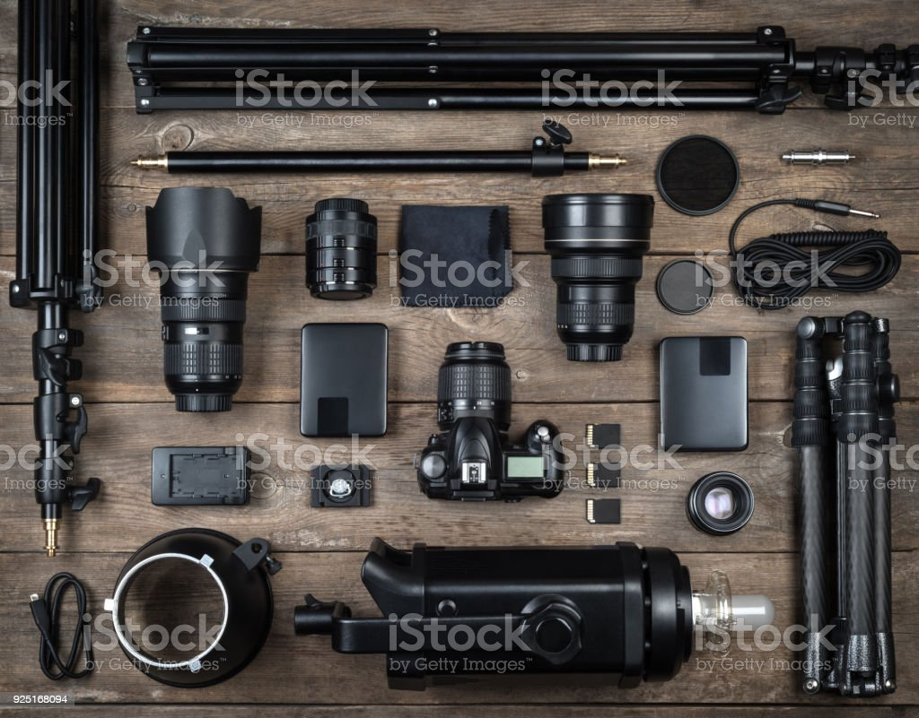 Set of the camera and photography equipment (lens, tripod, filter, flash, memory card, hard desk, reflector) on wood desk. Professional photographer accessories background. stock photo