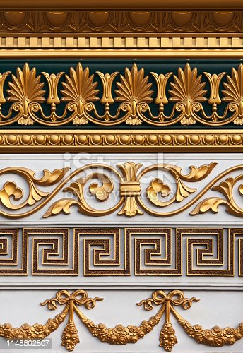 A set of the stucco molding of different styles covered with gold for decoration of internal space of the house.