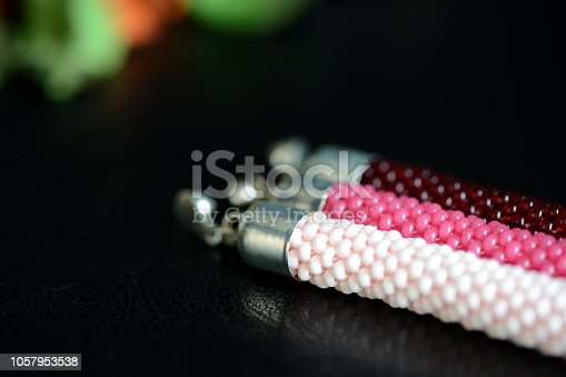 Set of three beaded bracelets on a dark background close up