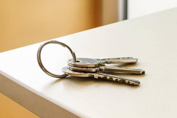 jogo de três chaves da casa no anel na tabela em um quarto. grupo do close-up das chaves do apartamento. para esquecer as chaves em casa consept. - chave - fotografias e filmes do acervo