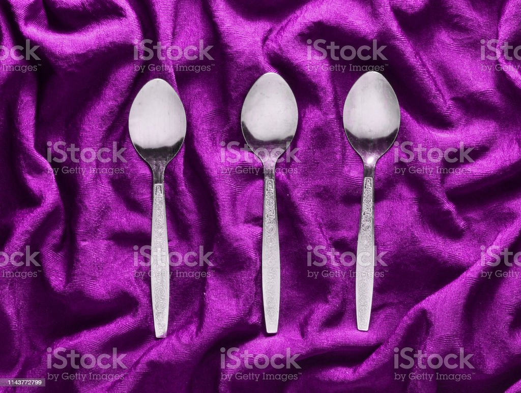 A set of three metal spoons on purple silk tablecloth. Top view.