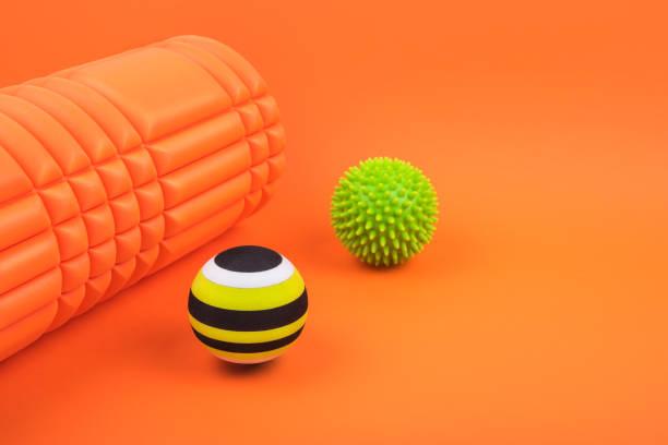 Set von zwei grünen myofascial Release und Massagekugeln, holprige Schaum Massagerolle für Triggerpunkte über gebrannten orange Farbhintergrund. – Foto