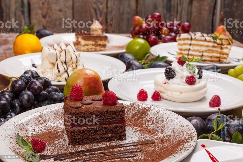 Set of various desserts on a wooden table decorated with fruits and berries. stock photo