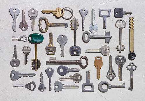 istock Set of various keys on rough concrete surface close-up 957878948