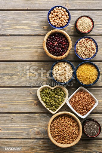 A set of various superfoods , whole grains,beans, seeds, legumes in bowls on a wooden plank table. Top view, copy space