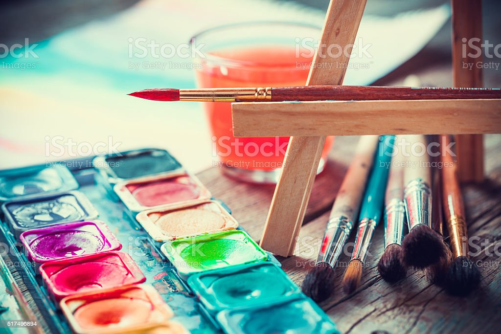 Set of watercolor paints and paintrushes for painting closeup. stock photo