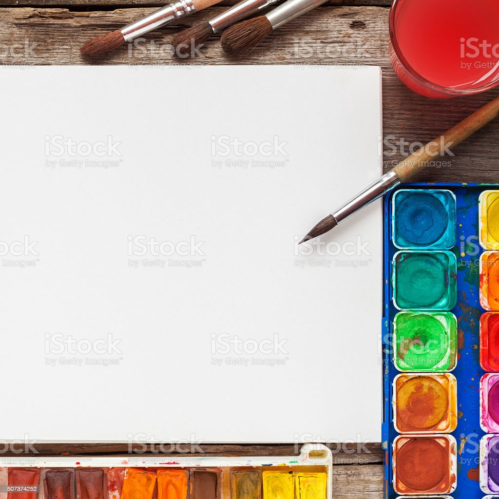Set of watercolor paints, brushes for painting and white paper stock photo