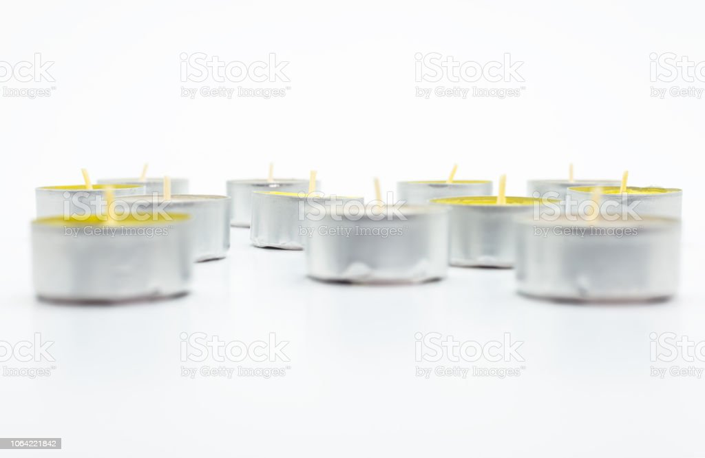 Eine Reihe von weißen und gelben Teelicht Paraffin Kerzen liegt auf einem weißen Hintergrund mit einem Beschneidungspfad. – Foto