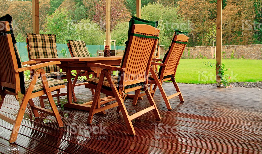 Set of wooden patio tables and chairs outside on wet garden stock photo
