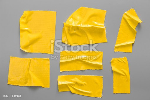 istock Set of yellow tapes on gray background. Torn horizontal and different size yellow sticky tape, adhesive pieces. 1001114260