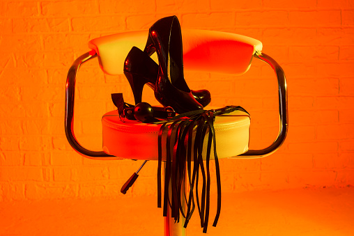 Bdsm Set On The Chair Shoes Gag And Whip Stock Photo - Download Image Now