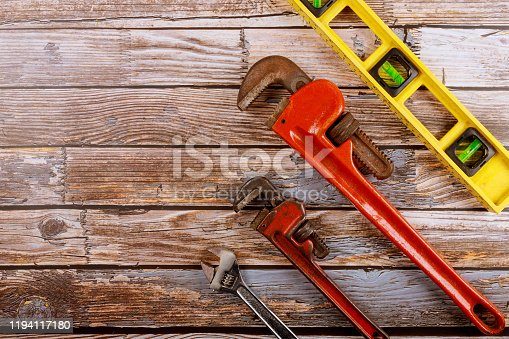 Plumbing set adjustable wrench with construction level on wooden board.