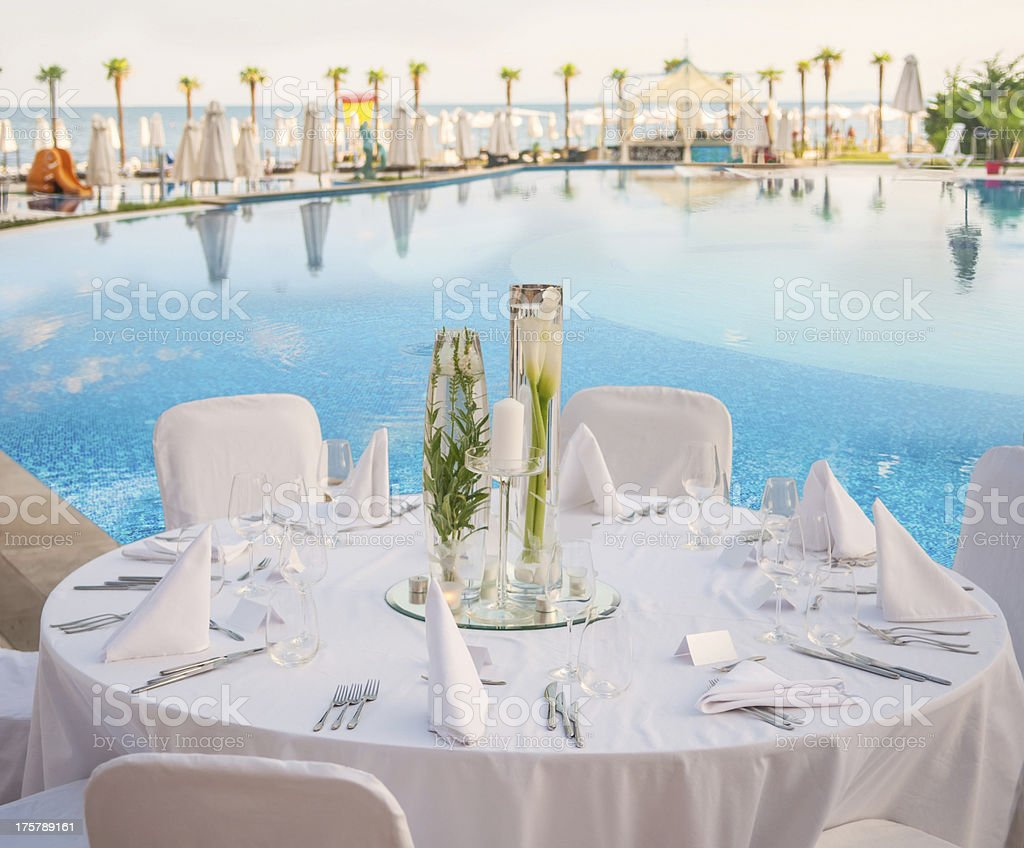 Set, round table with centerpieces overlooking water stock photo
