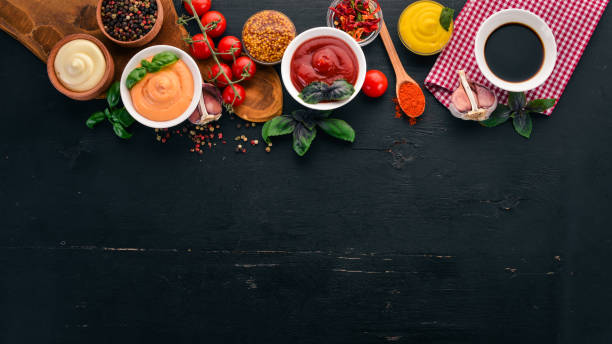 Set the sauces on a black wooden background. Ketchup, mayonnaise, mustard, soy sauce, barbecue sauce, pepper and spices. Top view. Free space for text. stock photo