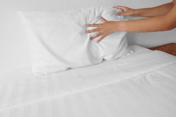 einrichten von weißen kissen auf bettlaken in hotelzimmer - verwandlungskissen stock-fotos und bilder