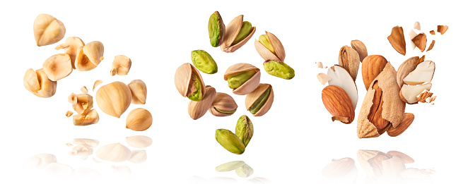 A set with Flying in air fresh raw whole and cracked pistachios, almonds and hazelnut isolated on white background. Concept of Pistachios almonds and hazelnut is torn to pieces close-up. High resolution image