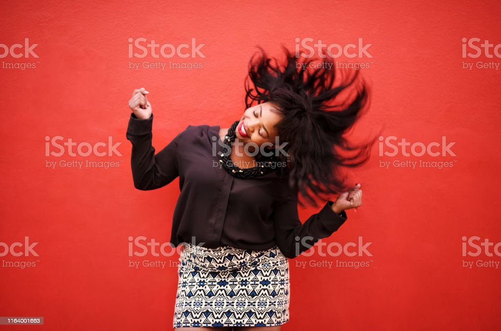 Set yourself free Shot of young woman dancing with short hair shaking her head over red background 25-29 Years Stock Photo