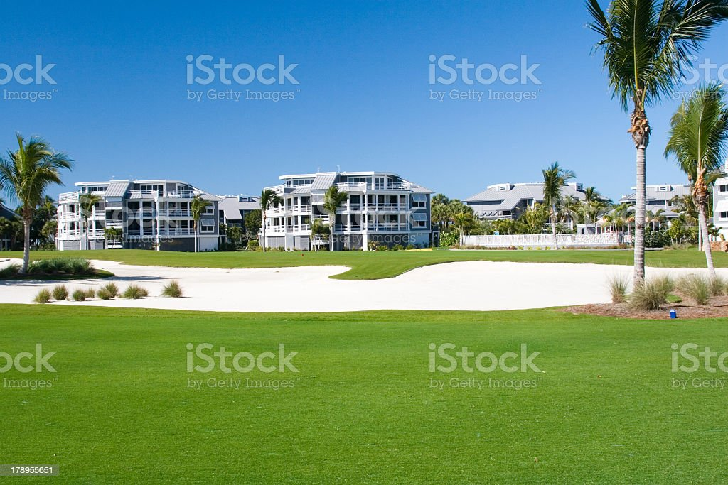 Sets of condos sitting on a golf course behind sand bunker stock photo