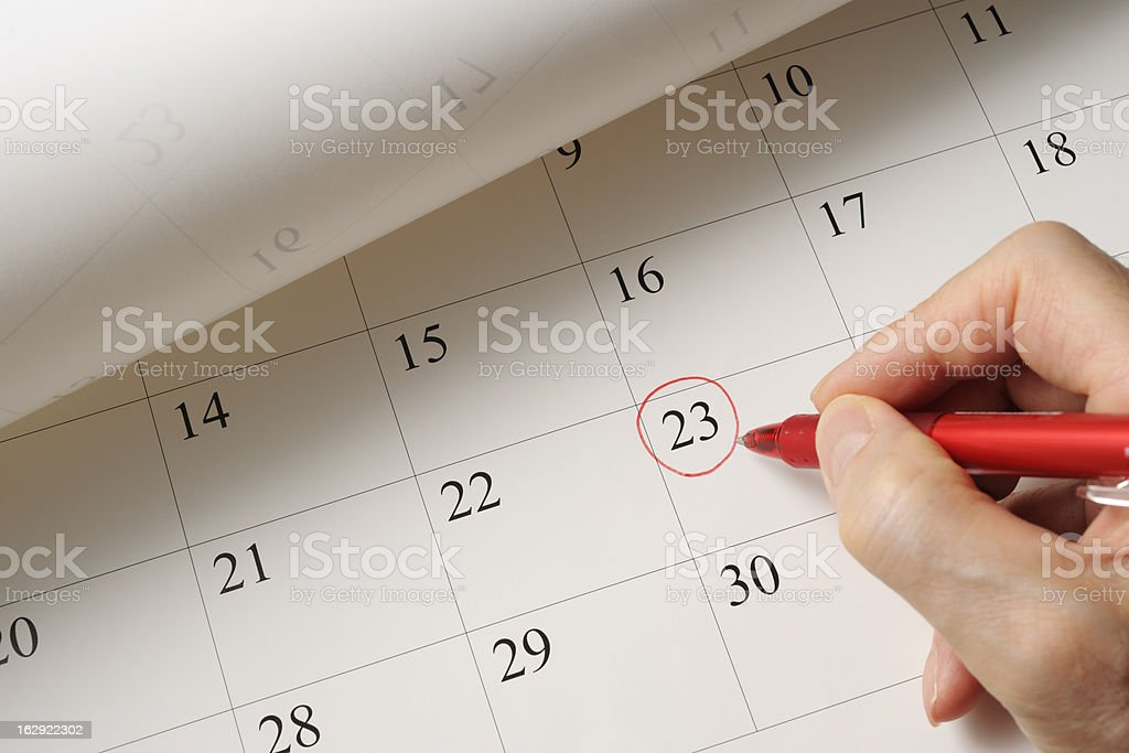 Setting a date on calendar by red pen stock photo
