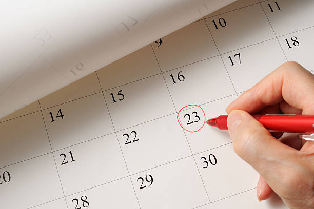 setting a date on calendar by red pen - calendar date stock photos and pictures