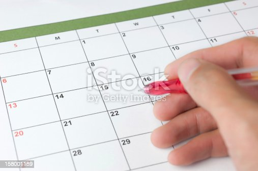 The right hand with a red pencil on the calendar